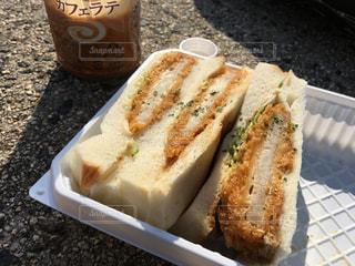 屋外で食べるサンドイッチの写真・画像素材[2099395]