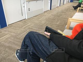 病院の待合の椅子に座っている男性の写真・画像素材[2807975]