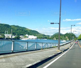 田舎の港町を走る道路と山の景色の写真・画像素材[2113738]