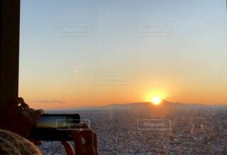 夕日を背に見える富士山と撮影する人の写真・画像素材[2122632]