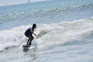 海のサーフボードに波に乗る人の写真・画像素材[2386969]