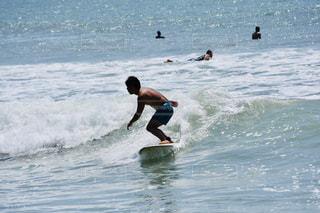 海のサーフボードに波に乗っている男の写真・画像素材[2448823]