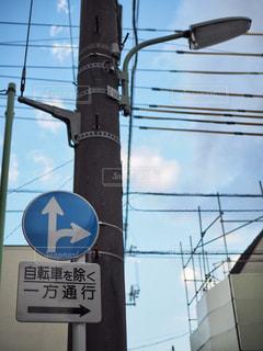 建物の側面を離れて掛かる道路標識の写真・画像素材[1163055]