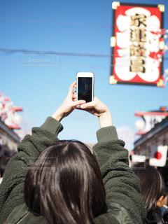 携帯電話で見ている人の写真・画像素材[1700987]