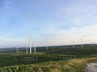 背景に風車と緑豊かな草原の写真・画像素材[2086290]