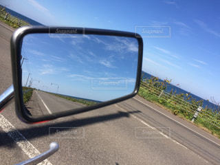 バイクのミラー越しに映る海とまっすぐに伸びた道路。の写真・画像素材[2088603]