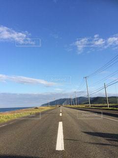 道路脇の海と電信柱の写真・画像素材[2088963]