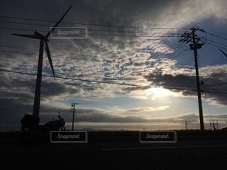 道路脇に広がる風車と電信柱とバイクの写真・画像素材[2089252]