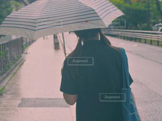 傘を持って歩道に立っている人の写真・画像素材[1416360]