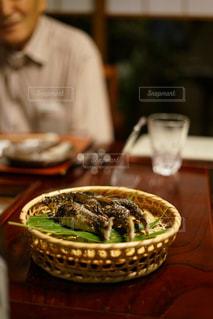 食べ物のボウルを持ってテーブルに座っている人の写真・画像素材[2442781]