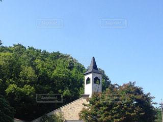 建物の側面に時計がある大きな背の高い塔の写真・画像素材[2106664]