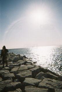 岩の多い浜辺に立つ人の写真・画像素材[2266643]