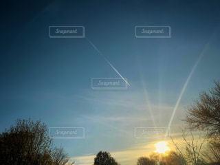 夕日に伸びる飛行機雲の写真・画像素材[2125143]