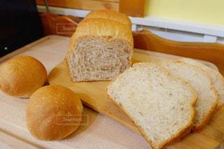 木製のカッティングボードの上にある手作りの食パンとロールパン。ロールパンはカットしてるところの写真・画像素材[3136159]
