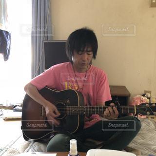 ギターを弾いている男性の写真・画像素材[2101084]
