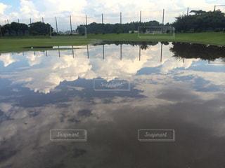 大雨の後の水たまりに反射する青空の写真・画像素材[2101553]
