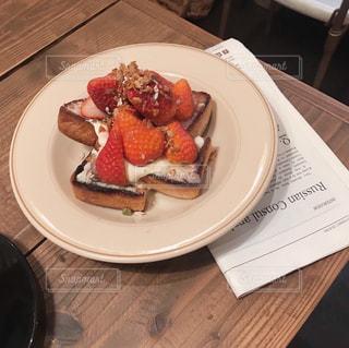 木製のテーブルの上に座っている食べ物の皿の写真・画像素材[2103113]