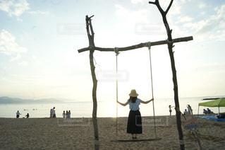 浜辺のブランコに乗っている人の写真・画像素材[2214683]