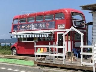土の道を下る赤い二階建てのバスの写真・画像素材[2105169]