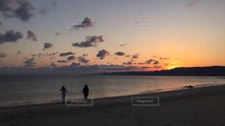 夕陽の照らす海岸を歩く2人の写真・画像素材[2112475]