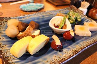 皿に食べ物の皿をトッピングした木製のテーブルの写真・画像素材[2110171]