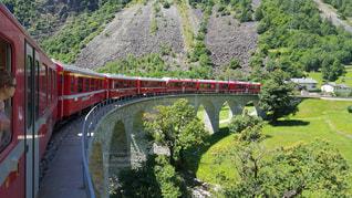 緑豊かな丘の中腹を旅する列車の写真・画像素材[2110274]