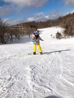 雪に覆われた斜面をスキーに乗っている人の写真・画像素材[2110366]