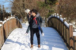 雪に覆われた橋を渡って歩いている男の写真・画像素材[2110949]