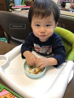 食卓に座っている小さな男の子が食べ物を食べているの写真・画像素材[2111512]