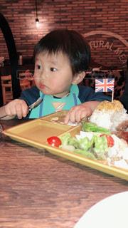 食べ物の皿のあるテーブルに座っている小さな男の子の写真・画像素材[2111513]