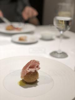 テーブルの上にケーキの一部をトッピングした白い皿の写真・画像素材[2117833]