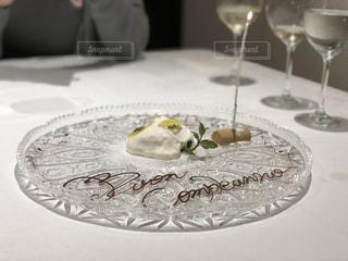 ワインのグラスの横にある皿の上の一枚のケーキの写真・画像素材[2117836]
