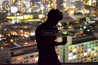 夜景を見下ろしながらカップアイスを食べる男の写真・画像素材[2117467]