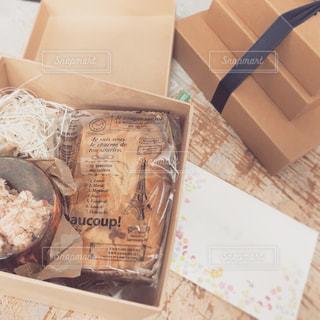 テーブルの上に座って食べ物でいっぱいのボックスの写真・画像素材[1228781]