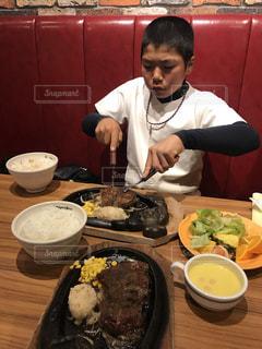 食べ物の皿を持った食卓に座る人の写真・画像素材[2119834]