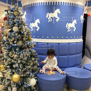 クリスマスツリーの横で椅子に座る女の子の写真・画像素材[933681]