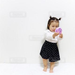 ペロペロキャンディを見つめる1歳の女の子の写真・画像素材[1095305]