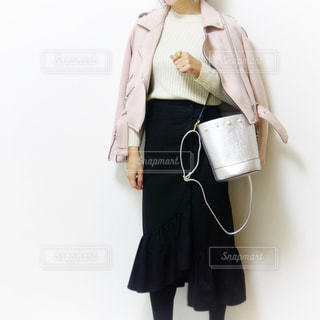 フリルスカートにライダースジャケットを肩がけした顎から下の女性の写真の写真・画像素材[1100775]