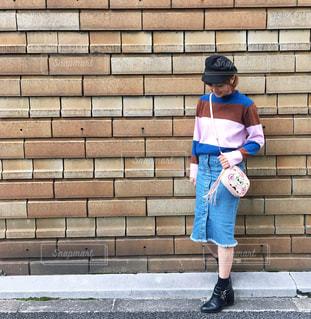 ピンクのマルチボーダーニットにデニムスカートを合わせた女性の輻輳の写真・画像素材[1100777]