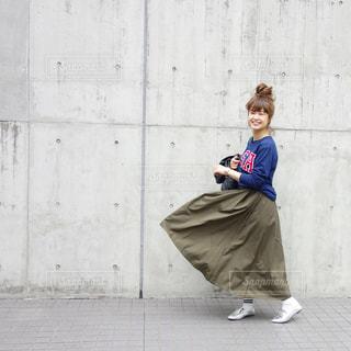 ロングスカートが恐怖でふんわりなびいたカジュアルコーデの女性の写真・画像素材[1100779]