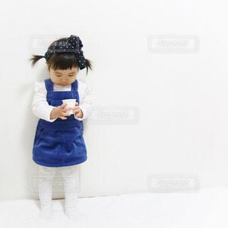 部屋に立って紙コップを持って下向いている1歳女の子のコーデの写真・画像素材[1105695]