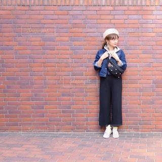 れんが造りの建物の前に立っているベレー帽を被った女性のコーデの写真・画像素材[1105701]