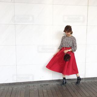赤いスカートに花柄スカートの女性の全身コーデの写真・画像素材[1105702]