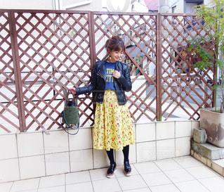 フェンスの横に立っているライダースコーデの女性の写真・画像素材[1105711]