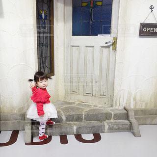 建物の前に立っている女の子の写真・画像素材[1105728]