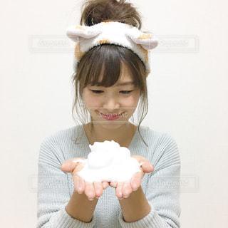 もこもこ泡を両手に乗せてヘアターバンをつけてスキンケアする女性の写真の写真・画像素材[1105768]