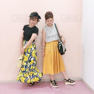 黄色の花柄ロンスカと黄色のスカートコーデで並んで下を向いた女性2人の写真・画像素材[1105781]