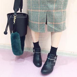 ワンピースを着て立ってバックを持っている女性の足元の写真・画像素材[1105786]