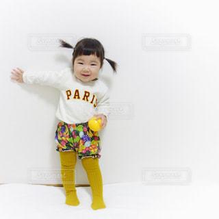フルーツ柄のパンツコーデでオレンジのおもちゃを持って笑う女の子の写真・画像素材[1105793]