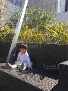 品川グース内のガーデンカフェの椅子に座る女の子の写真・画像素材[1105798]